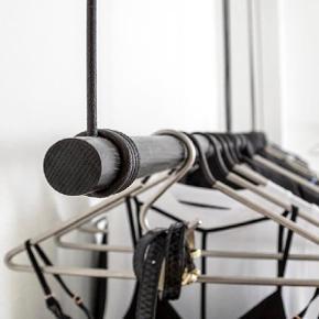 Garderobestang  WALL SWING fra LIND DNA til din entre eller garderobe. Minimalistisk knage til bøjler. Wall Swing er produceret i Danmark i egetræ og med lædersnor til ophægning.   Monterer SWING med pluks og krog i loftet. Lædersnoren tilpasses i højden og spændes efterfølgende med medfølgende beslag.   Længde: 80 cm, højde ca 50 cm. Der medfølger sorte S-kroge til ophæng.  cm. 2 år gammel, sælges pga flytning. Nypris 1500kr Afhentes i Odense C.
