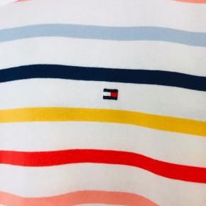 Super flot Tommy Hilfiger T-shirt i friske farver. Kun brugt et par gange. Fremstår som ny. Let figursyet, sidder til. Brystmål: 48 cm foran og det samme bagpå Længde:  68 cm   *Kom også gerne med et bud*