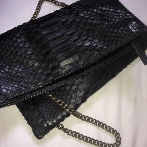 Ægte pyton taske fra Dharma Copenhagen i sort.  Har ét stort rum når man åbner den med et mindre lynlåsrum indvendigt og udvendigt.  Nypris: 2400kr Sender med DAO - Køber betaler fragt 🌈