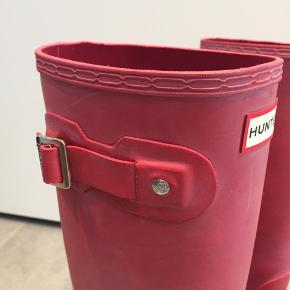 Røde gummistøvler fra Hunter i str. 38. Sælges med eller uden indersokker, der giver ekstra varme. Indersokker koster 75,- og sælges også seperat.