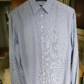 "Klassisk med et twist skjorte fra D&G med ""dobbelt"" lomme front. Skjorten er hvid og blå stribet og  I STR.42 hvilket er L. passer også til en M. Beklager den dårlige pixelering men trendsales og striber spiller bare ikke sammen  Mp 500"