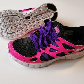 Nike Air Free Customised i pink, sort og lilla. De er brugt et par gange indendørs og fremstår derfor praktisk talt som ny.