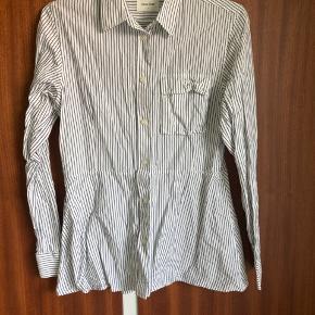 Skjorte med mørkeblå striber. Fine detaljer som peplumeffekt og brystlomme.  Fra dyre- og røgfrit hjem ✨
