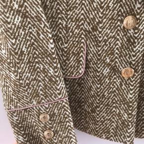 Flot blazer fra Baum und Pferdgarten. Guld knapper samt pink kant ved lommer og ærmer.💫💗  Mål på blazeren:  📏✏️ Hel længde ca. 62 cm Brystmål ca. 44 cm Arm længde ca. 61 cm