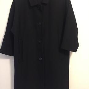Sort frakke fra COS med trekvartlange ærmer. Kun få tegn på slid hvor stoffet ser lidt blankere ud end ellers.