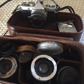 """Retro-kamera fået af min far. Kameraet virker, men er ikke blevet brugt i flere år, siden jeg fik det, så det kunne trænge til, at en person med styr på den slags kameraer, kan give det """"nyt liv"""". Der hører en masse dele med - både de dele som ligger i den brune kamerataske + en pose med flere linser osv."""