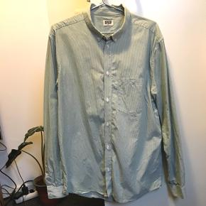Langærmet skjorte med lysegrønne og hvide tynde striber fra Weekday. Den er ikke brugt særlig meget, så den fejler intet.