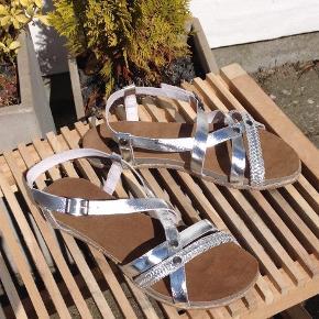 Varetype: HELT NYE skind sandaler fra SOON sølv Farve: Sølv Oprindelig købspris: 500 kr.  HELT NYE  Skindsandaler fra danske SOON - sølv Skind indersål og justerbar skind rem Indv. sållængde ca. 25,5 cm  KUN kr. 200,- (butikspris kr. 500,-) + porto kr. 45,-