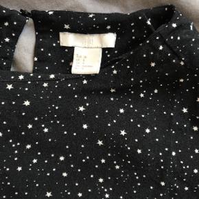 T-shirt med hvide prikker, og knaplukning i nakken.  Den er brugt, og krøller i stoffet efter brug.  Derfor sælges den billigt.