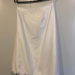 Hvid nederdel fra Lilly. Størrelse 40. Måler 2 x 35 cm i livvidden og 64 cm lang.