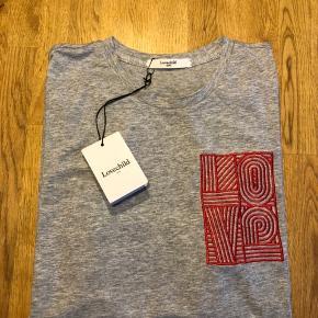 Cool grå t-shirt fra Lovechild. T-shirten har en løs pasform, er af en blød bomulds-kvalitet, samt har et rødt statement logo på venstre bryst.   Mål str. L (svarer til en medium / large - 38/40) Bryst omkreds: 98 cm Længde: 64 cm  Nypris: 499,- Materiale: 100% bomuld.  Respekter venligst at jeg ikke bytter og køber betaler porto samt gebyr ved tspay (sælger og købers gebyr).