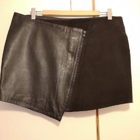 Fed nederdel i læder. Nederdelen har skrå lynlås lukning foran og indvendig knap som ekstra sikring.