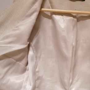 Flot og velsiddende sandfarvet blazer fra Zara. Desværre er foret revnet ved ærmerne. Sælges billigt.