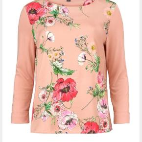 Skøn printet bluse fra Gustav. Blusen har bådudskæring, lange ærmer og et flot blomsterprint på fronten, mens ryggen er ensfarvet rosa. Pasformen er løs og let 🌸💕