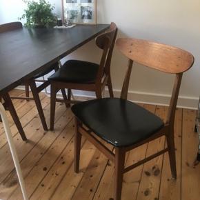 """4 stk retro stole i teak og med sorte nappa-sæder. Muligvis Farstrup-stole - der er intet stempel, men de ligner utrolig meget de klassiske stole fra Farstrup Møbelfabrik. Stolene fremstår med brugsspor og mindre skader. En enkelt stol har et lille hul i nappaet, en enkelt stol mangler en """"træknap"""" og har slået lidt af finéret af, og på en enkelt af stolene er en tværpind knækket (se billederne). Alle stolene trænger til at blive skilt ad, udrenset for gammel lim, samlet og limet på ny, da stellet flere steder er begyndt at løsne sig. Da stolene trænger til en kærlig hånd, sælges de billigt. Stolene kan dog sagtens renoveres. Hvis man er lidt handy, kan man gøre det selv. Alternativt kan en snedker gøre det. Sælges samlet og skal afhentes på Amager, 1. sal."""