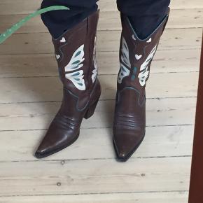 Sæsonens it-trend, cowboystøvler! Brune læderstøvler med sommerfuglemotiv i beige/turkisgrøn fra Nine West, str. 38. Rigtig god stand.
