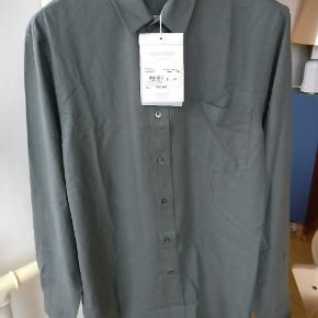 Our legacy classic shirt i silke og med knapper af perlemor. Farven er dull gray, en grå/grøn nuance er mit bedste sproglige bud.  Str. er 50 passer en M/L Mp. 775