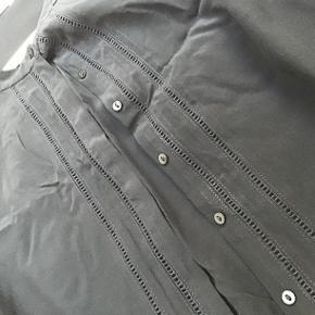 Skøn skjorte sælges, knappes foran. Fint hulmønster foran og små læg bagpå. Brystmål : 2x62 cm Længden 67 cm.
