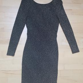 Smuk glimmerkjole fra H&M. Selve stoffet er sort med bittesmå glimmerstykker der giver en flot glimtende effekt over hele kjolen. Kjolen er åben i ryggen med en guldfarvet lænke øverst.  Velsiddende kjole der nemt kan passe en str. S pga. elastikken i stoffet. Har aldrig fået brugt den så den er helt ny.