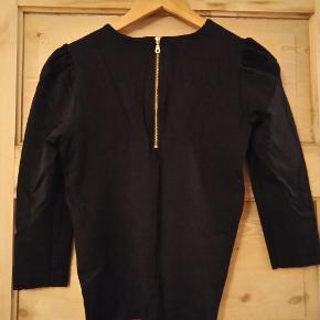 Bluse i kraftigt stof med en del stræk i. Guldfarvet lynlås bagpå. Fine, små læg på ærmerne ved skuldrene.