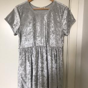 Fin, sølvfarvet t-shirtkjole i velour. Kun brugt få gange, da den er lidt for kort til mig (jeg er 180cm). Fejler ingenting. Kan hentes på Amager eller sendes. Køber betaler fragt.