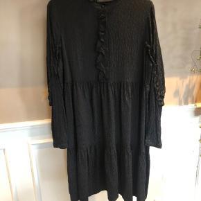 Fin kjole i sort med jacquardvævet mønster og fine flæsedetaljer. Kun brugt en enkelt aften og fejler intet.  Mindstepris 300,- pp.  BYTTER IKKE!