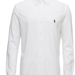 Hvid Ralph Lauren Polo skjorte Custom Fit str. M. Aldrig brugt og ligner en splinterny skjorte. Købt for 899,- men sælges for 599,-.  Billedet er fra google, da jeg står midt i en flytning og ikke har den ved siden af mig. Ved interesse kan jeg skaffe billeder af den.