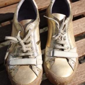 Brand: Cocomo Varetype: Sneakers Farve: Guld,   Gylden Oprindelig købspris: 699 kr.  Rigtig smukke og feminine robuste sko med god blød gummisål.   Brugt få timer og med meget lidt slid - se billeder for bedømmelse.  Også rigtig god til den smalle og slanke pigefod, da den kan spændes ind henover foden med velcrostrap.   Ca. længde på indvendig sål: 25 cm  DAO u/omdeling