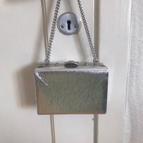 Fin lille sølv taske med kædehank. Tasken har et rum med kort lomme. Kæden måler ca. 74 cm. Tasken måler:  Bredde: 15 cm Højde: 11 cm Dybde: 7 cm