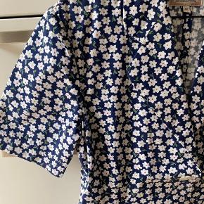 Skjorte i et smukt liberty print, som er købt vintage/secondhand, men i meget fin stand og uden slid eller tegn. Knapperne er formet som blomster og der er små lommer foran. Jeg har ikke gået med den selv. Den er en 42, men meget lige i str. den svarer til en 36 - 38 / small-medium. Den kommer fra et ikke-ryger og ikke-dyre hjem. Er ikke brugt efter den er købt vintage - jeg beklager billeder af at den ikke kan lukkes, men jeg kan ikke passe den.  Respekter venligst at jeg ikke bytter og køber betaler porto samt gebyr ved tspay.  Mål:  Brystmål: 45 cm (målt ligeover) Talje: 38 cm (målt ligeover) Længde: 60 cm (målt fra skulder og ned)