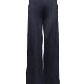 Dette par bukser med klassisk talje er udsmykket med syede pressefolder, som giver stylen et skræddersyet look.  Materiale: 64% viskose, 30% polyester, 6% elastan. Mål str. XS: talje 33,5cm, livhøjde forside 25cm, hofte 40,5cm, lårvidde 28,5cm, benlængde 76,5cm.   Bukserne er brugt, og har lidt fnuller hist og her, hvorfor standen er sat som den er.