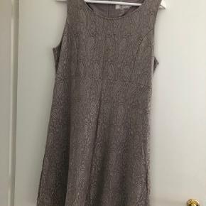 En super flot, fest kjole! Brugt 1 gang. Farve er sådan lidt sand/grå. Mønster i stoffet.  Kan desværre ikke passe den. Virkelig flot