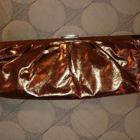 Varetype: Sjov clutch med tilhørende, lang kæde Størrelse: Stor Farve: Bronze  Skøn, stor clutch i farven bronze med tilhørende lang skulder-kæde. Længde 33 cm. Højde 12,5 cm og dybden er 3 cm. Kildemateriale. Aldrig brugt. BYTTER IKKE!!