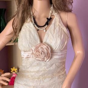 Super sød beige top m/ stor rose foran. Bindes i nakken m/ langt silke bånd. ( rosen på Bill. Ser lyserød ud, MEN den er samme farve som toppen - beige)  Brugt , men pæn .  Mærke: do & bé   100% polyester