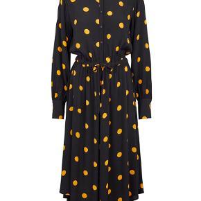 Super fin kjole sort med orange dots i størrelse M fra Just Female. Kjolen er vasket 1 gang men aldrig brugt. Desværre for lille. Kjolen er gennemknappet i det øverste stykke og har elastik med bindebånd i taljen, hvilket giver en flot figur. Kina krave og manchetter ved ærmerne. Asymmetrisk forneden hvilket giver kjolen et lækkert touch.  Kvalitet: 100% Viskose