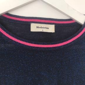 Fin Modström bluse i tyndt strik med glimmer og lyserøde detaljer i halsen og på ærmerne. Kun brugt få gange. Fremstår som ny.