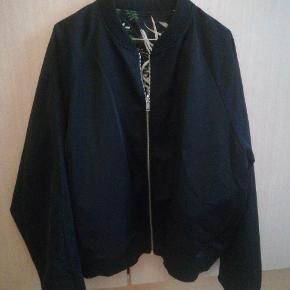Vendbar jakke, mønstret på den ene side og sort på den anden