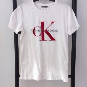 Calvin Klein tshirt med rødt logo i velvet sælges.  Er brugt 2 gange og fremstår som helt ny.   StrM -størrelsessvarende. Dog er den ikke over size.   Np:500kr Mp:250kr  Kan sendes på købers regning