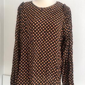 Fin rummelig tunika med lange ærmer og elastik i ærmerne. En lille fin flæse på skulderen. 70% viscose, 30% silke.