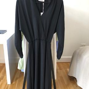 Helt ny kjole fra Moss Copenhagen sælges. Kjolen har v-udskæring samt elastik i taljen, der gør den yderst feminin og elegant. Kan både bruges til hverdag og fest. Køber betaler fragt, hvis varen skal sendes.