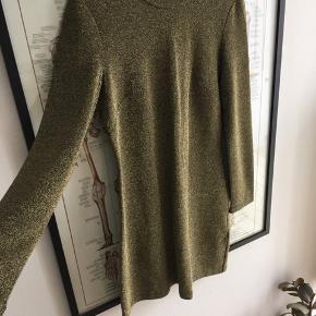 Lækker fitted mini dress i guldglimmer, lange ærmer og lynlås i ryggen. Brugt 2 gange.  Kjolens elastiske stof gør at kjolen sidder helt perfekt.  Materiale: viskose/ polymid/ elastan Længde fra skulder: 90 cm Kan afhentes på Østerbro eller sendes med DAO (39 kr). Køber betaler Porto