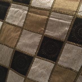 Smukt stort håndsyet sengetæppe i råsilke i farverne sølvgrå, gylden og sort. 270 x 225 cm. Fire pudebetræk følger med. Nyt og aldrig brugt.