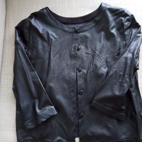 """Lækker sort jakke/bluse, der kan anvendes med knapper både foran og bagpå. Behagelig tynd """"skind""""kvalitet, med blødt stofbeklædning indvendigt. Fin både som lille jakke uden på kjole eller som bluse."""