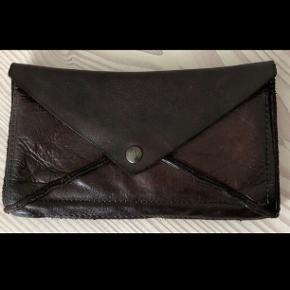 Flot mørkebrun pung fra Maledetti Toscani -håndlavet i 100% vasket Buffalo læder. Købt i Italien og brugt i en måned, fremstå som da den blev købt;) Der er et rum med lynlås til mønter, plads til 6 kort -og to rum. Lukkes med knap. Np: 890 kr Måler: 21x12 cm  Kommer fra røgfrit hjem.
