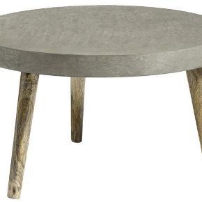 Rundt spisebord I flot beton look med bordben af træ fra Unoloving.  Størrelse: Ø110 2 år gammelt men ingen skader. Kvittering haves stadig.