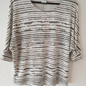 Oversize bluse fra Vero Moda, hvid med stribet print i gråt, 3/4 ærmer med ribkant, lavet af polyester og viskose.  Let fnuller på forsiden (se sidste billede).  Prisen er ekskl. forsendelse.