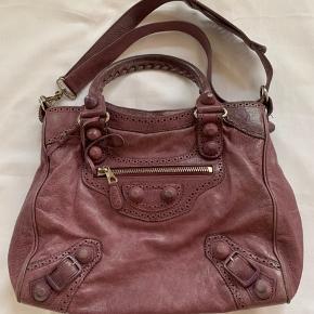 Balenciaga Velo taske i lilla. Tasken er brugt en del med stadigvæk i fin stand. Lidt slitage ses betrukkede studs. Originalt spejl og dustbag medfølger.  Mål: 33 x 14 x 30 cm