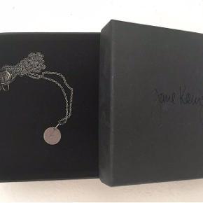 Den populære 'lovetag' halskæde fra Jane Koenig. Rhodineret sølv, ankerkæde i mellemlængden (60 cm) og mellem vedhæng (Ø 11 mm) med indgraveret 'A'.