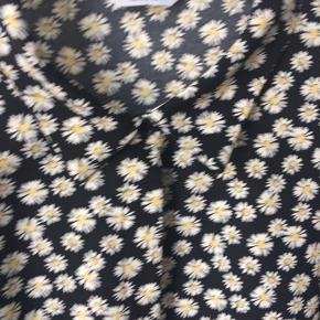 Lang skjortekjole i sort med hvid / gule blomster. Med slids og bindebånd Som ny - købt en tand for stor🙁