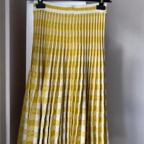 """Super cool nederdel (""""Cyrilla"""") fra Baum und Pherdgarten i en smuk gul farve.  Nederdelen har medi-længde og har en plisseret effekt. Stoffer er lavet i en strikket elastisk kvalitet og taljen er derfor strækbar. Nederdelen har et fint grafisk print og indvævede lurex-glimmertråde.  Aldrig brugt (prismærke sidder stadig på). Sælger kun og bytter ikke.  Mål:  Talje : 34 cm  Talje (udstrakt): 39 cm, længde: 72 cm."""
